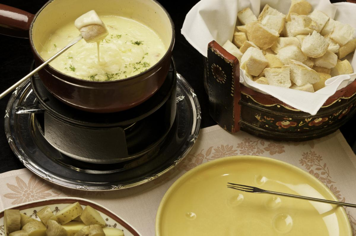 Traditional french fondue with bread cubes and boiled potatoes