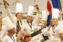 "U.S. chef Mathew Peters (center), celebrates on the podium with teammates after winning the ""Bocuse d'Or"" trophy, in Lyon. (Photo Credit: Laurent Cipriani/AP)"